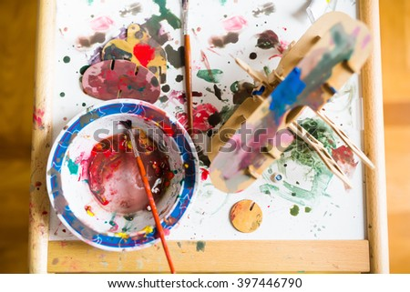Table with watercolors, brushes,and wooden parts of airplane toy. Young designer with many ideas waiting to be found. Shallow depth of field. - stock photo