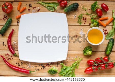 Table with white dish and Variety of fresh vegetables, tomato, pepper, cucumber, carrot, space for text on white. - stock photo