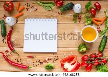 Table with white notebook and Variety of fresh vegetables, tomato, pepper, cucumber, carrot, space for text on white. - stock photo