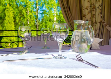 Table with white tablecloth. Photo of summer hotel complex.