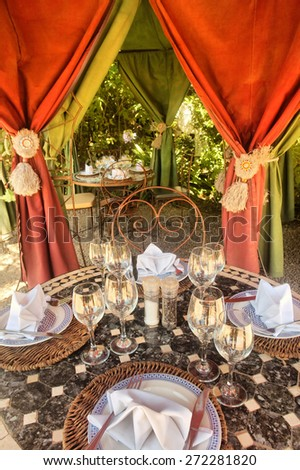 Table with wineglasses in outdoor pavilion. Shot in South Africa.  - stock photo