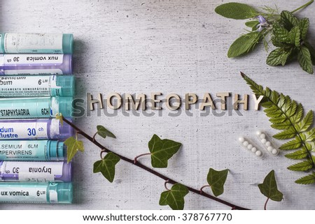 Table with written text Homeopathy, homeopathy globules and bottles - stock photo