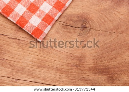Tablecloth red and white checkered wavy on wooden table - stock photo