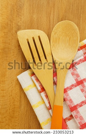Tablecloth, spatula and spoon on wooden table background, cooking concept