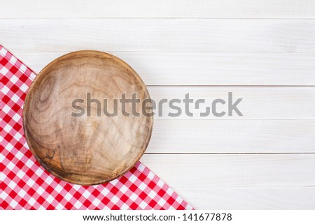 Tablecloth, wooden plate on table background - stock photo