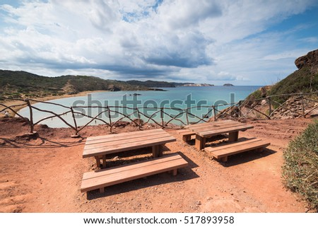 Tables and benches in Cavalleri­a beach, Balearic islands, Menorca, Spain.