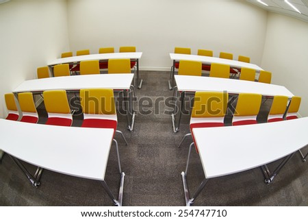 Tables and chairs in an empty classroom. Fish-eye photo - stock photo