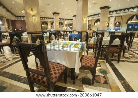 Tables and chairs in large luxury hotel restaurant with pillars