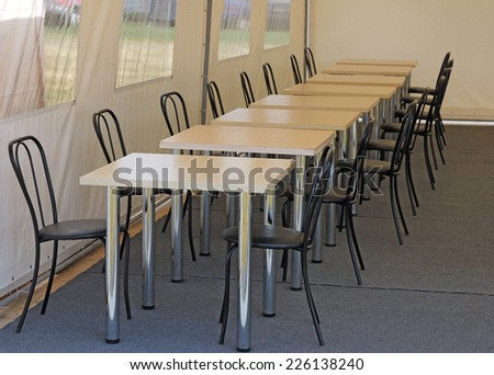 tables and chairs in the dining room in the tent camp. - stock photo