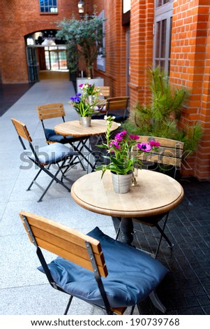 tables and chairs - patio of a restaurant - flowers and colorful walls - stock photo
