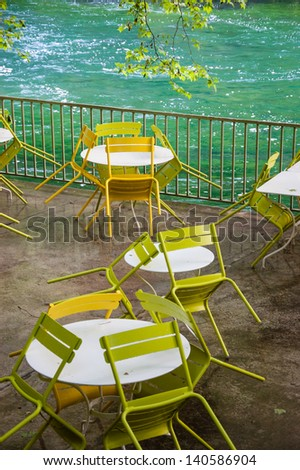 Tables and chairs with rain drops. Riverside cafe after closure in Provence.