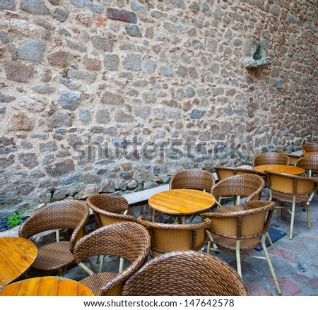 tables and wicker chairs in summer cafe near the ancient stone wall - stock photo