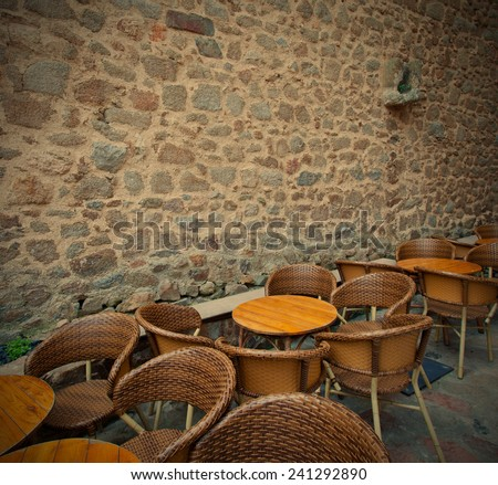 tables and wicker chairs in summer cafe near the ancient stone wall, instagram image style - stock photo