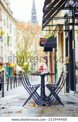 Tables of a Parisian outdoor cafe decorated for Christmas - stock photo