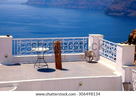 Tables on beautiful white terrace overlooking sea in Oia, Santorini, Cyclades, Greece - stock photo