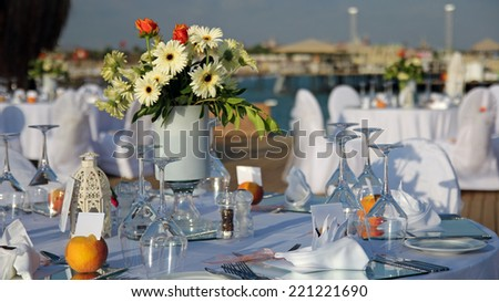 Tables Set Up For Wedding Reception. Outdoor Table Setting at Wedding Reception by the Sea. Wedding Chairs and covers at an outdoor wedding. Elegant Outdoor Wedding Table with Sea Views. - stock photo