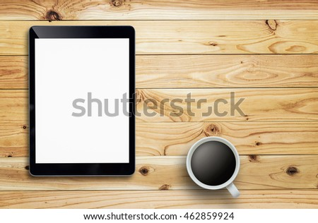 Tablet and coffee cup on wood table. tablet white screen. tablet white display.