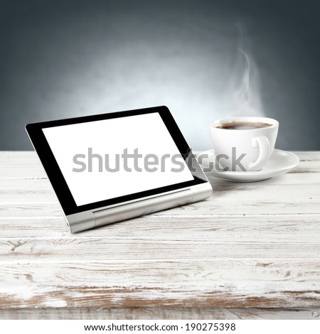 tablet and coffee cup with blue wall  - stock photo