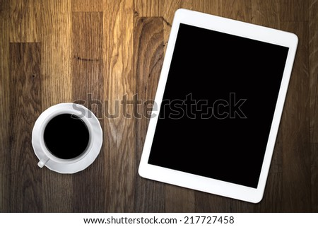 tablet and coffee on old wooden table
