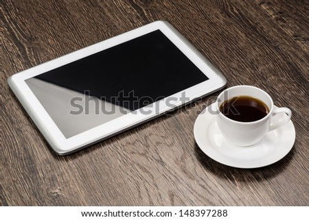 tablet and cup of coffee are on the table, still life - stock photo