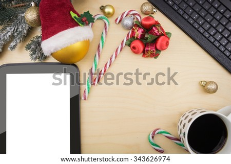 Tablet and cup of coffee with winter festive ornaments. - stock photo