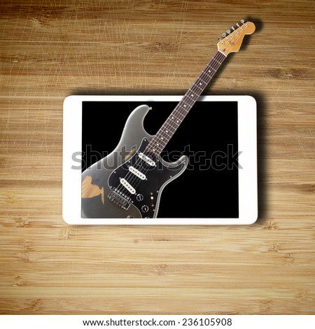 Tablet and guitar splashing out of it - stock photo