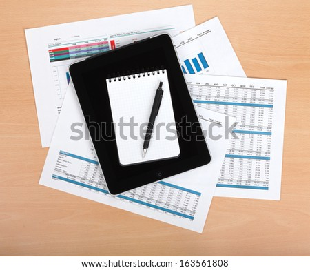 Tablet and notepad over papers with numbers and charts, coffee cup, glasses and pen. View from above - stock photo