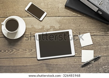 tablet and phone placed next to sticky notes on a wooden workplace - stock photo