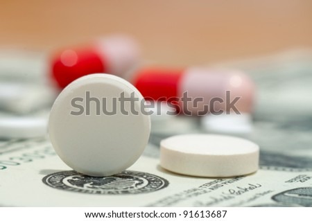 Tablet and pills on the 100 dollars banknote - stock photo