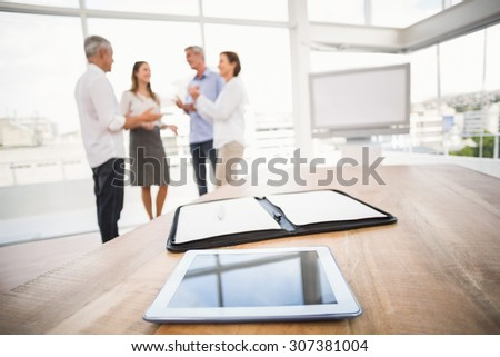 Tablet and planner in front of talking business people in the office - stock photo