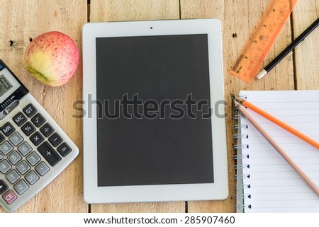 Tablet and red apple with school supplies on wooden table - stock photo