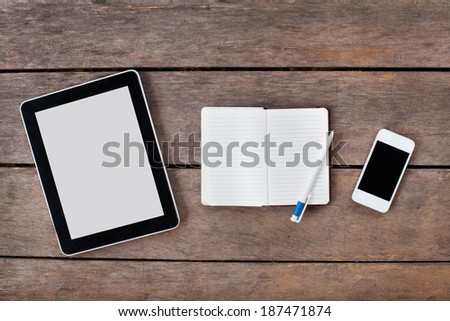 tablet and smartphone on wooden desk - stock photo