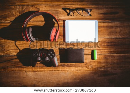Tablet and USB key next to glasses wallet and joystick on wooden table