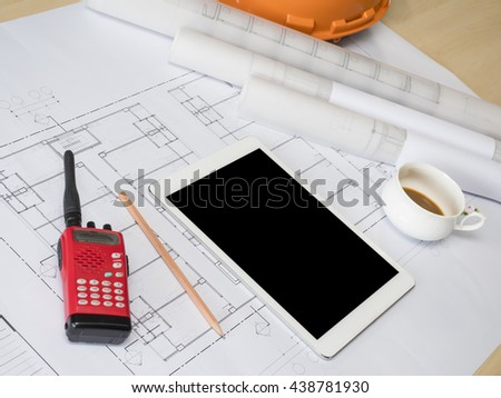 Tablet, Architect rolls and plans, technical project drawing on table (Selective focus) - stock photo