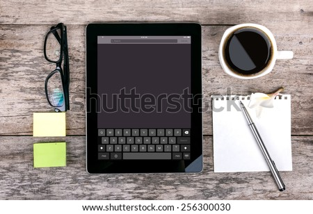 tablet as a keyboard glasses pen note paper calculator  with keyboard on screen on wood backgound - stock photo