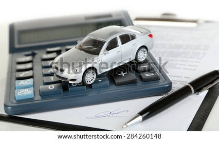 Tablet, calculator and toy car isolated on white - stock photo
