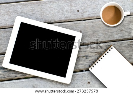 Tablet coffee cup and notebook on wooden background.