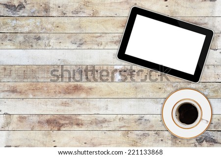 tablet computer and coffee cup on wooden background - stock photo