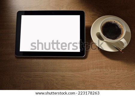 Tablet computer and coffee cup on wooden background