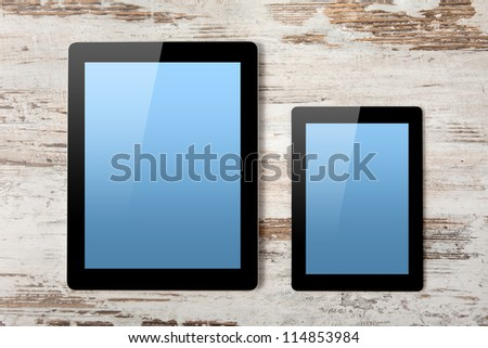 tablet computer and mini tablet with isolated screen on a background of wood - stock photo