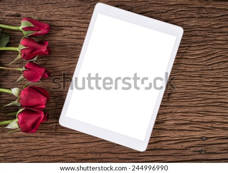 Tablet computer and red rose on old wooden background - stock photo