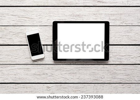 Tablet computer and white smart phone with isolated screens on white wooden desk.