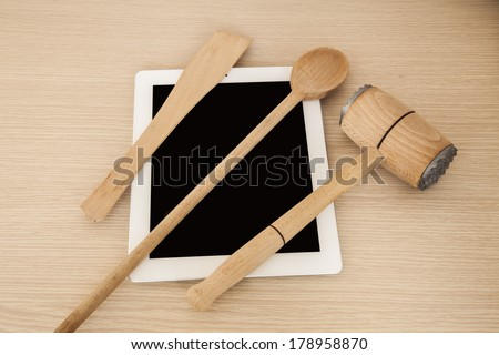 Tablet computer and wooden spoon, kitchen hammer and other wooden kitchen elements.  - stock photo