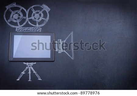 Tablet computer as movie camera on the blackboard with tripod and strobe drawn with chalk - stock photo