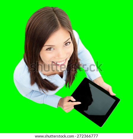 Tablet computer. Business woman using digital tablet computer PC happy isolated cutout on green background. Focus on both tablet and face. Woman in business shirt with finger on touch screen display.
