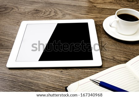 Tablet computer cup of coffee and notepad at table