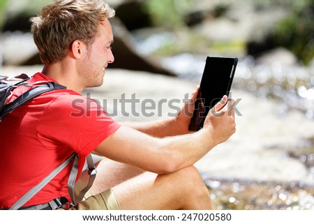 Tablet computer man hiker hiking in Yosemite, USA using travel app or map during hike, resting by river. Caucasian male hiker relaxing on a summer day. - stock photo