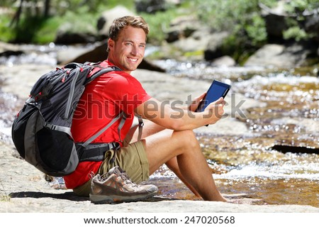 Tablet computer man hiker relaxing by river holding ebook reader reading e book or map, hiking in Yosemite, USA using travel app or map during hike. - stock photo