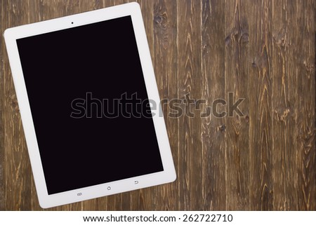 tablet computer on old wooden table - stock photo