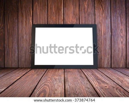 Tablet computer on wood background - stock photo